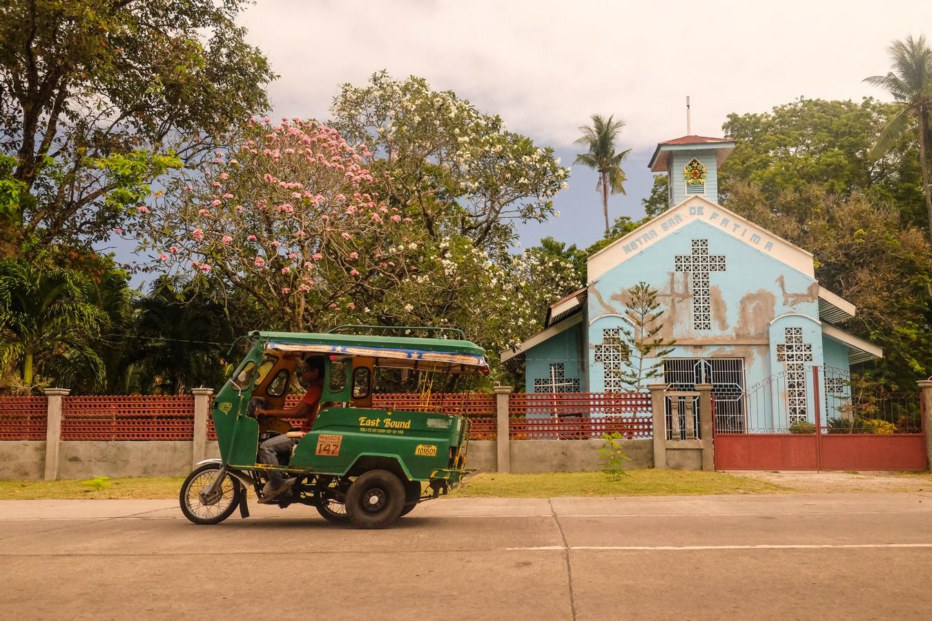 Photo d'une église chrétienne et d'un habal habal aux Philippines.
