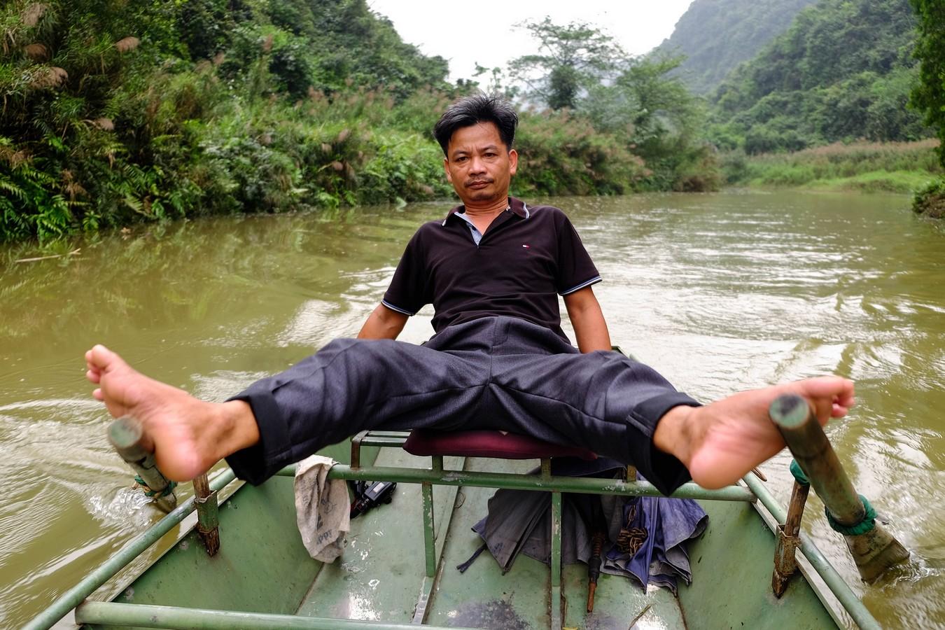 Batelier avec les pieds à Tam Coc au Vietnam