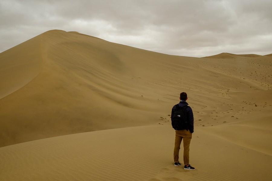 Le voyageur contemple les dunes de Dunhuang, Chine.