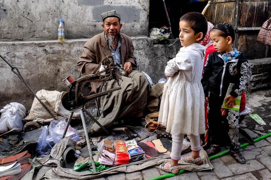 Cordonnier de rue dans les rues de Kashgar, Chine.