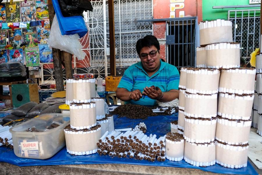 Roulage de cigarettes au tabac amazonien, au marché de Belen, Iquitos.