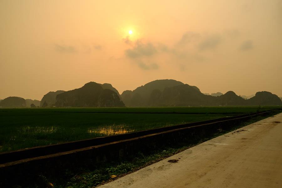 Soleil couchant sur les pics karstiques de Tam Coc, Vietnam.