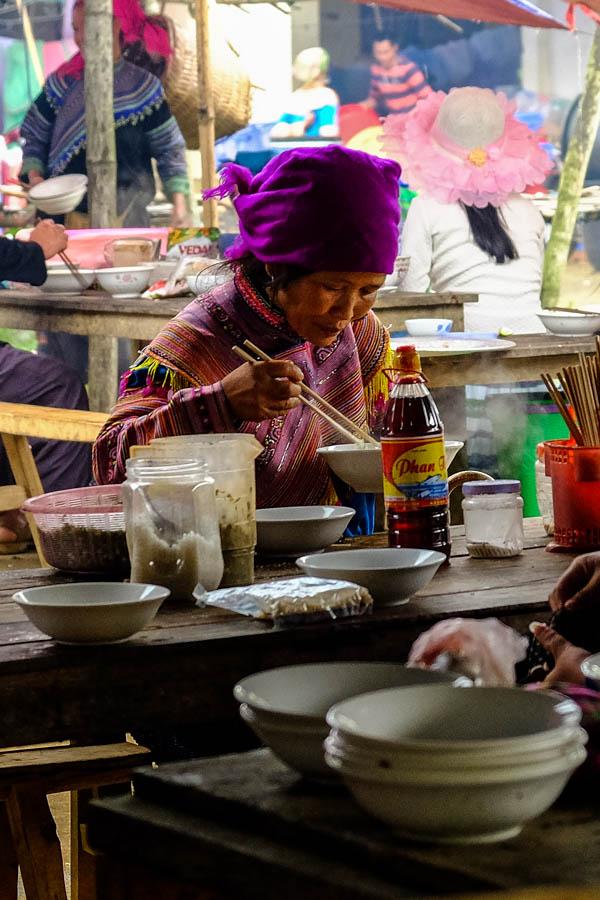 Femme Hmong mangeant un Phô au marché de Coc Ly, Vietnam.