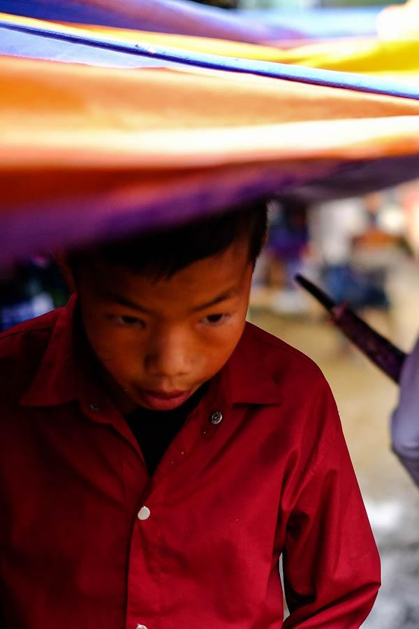 Jeune garçon sur le marché de Coc Ly, Vietnam.